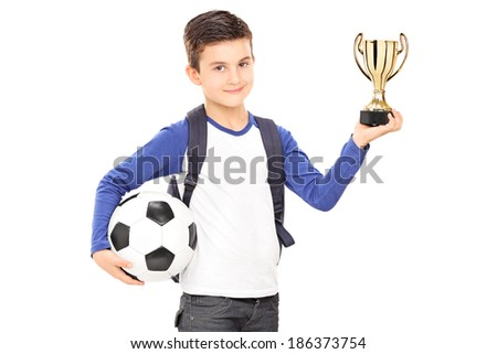 Little schoolboy holding football and a trophy isolated on white background - stock photo