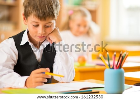 Little schoolboy  sitting behind school desk during lesson in school - stock photo