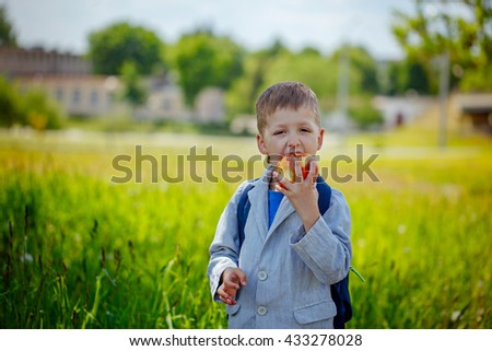 Little schoolboy with backpack and eating apple. Back to school outdoor - stock photo
