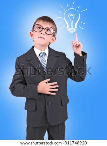 Little schoolboy with idea bulb above the head on blue background - stock photo