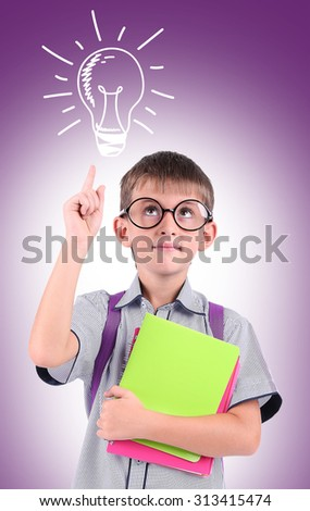 Little schoolboy  with idea bulb above the head on purple background - stock photo