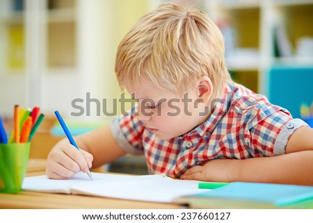Little schoolboy writing in copybook at lesson