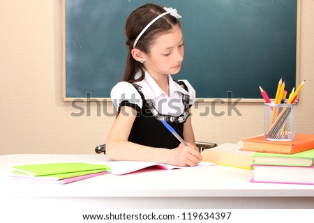 little schoolchild in classroom write in notebook