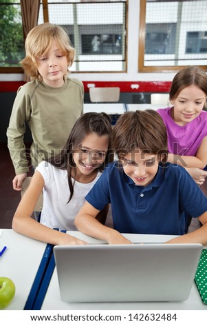 Little schoolchildren using laptop together at desk in classroom - stock photo