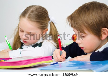 Little schoolchildren writing in workbook - stock photo