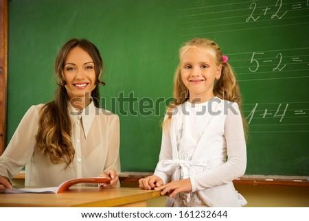Little schoolgirl answering near blackboard in school - stock photo