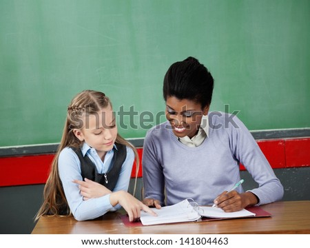 Little schoolgirl asking question to female teacher at desk in classroom