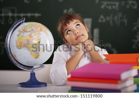 Little schoolgirl dreaming in classroom   - stock photo