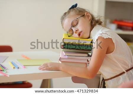 Little schoolgirl fall asleep on a pile of books.  It is elementary school student. Tired baby with glasses rested her head on the book. To kids difficultly long to be engaged. Back to school.