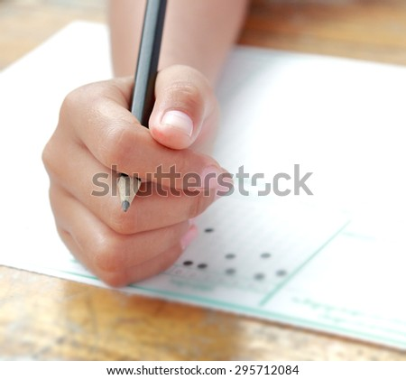 Little schoolgirl hand on examination answer sheet with black pencil in finger shot with wide aperture