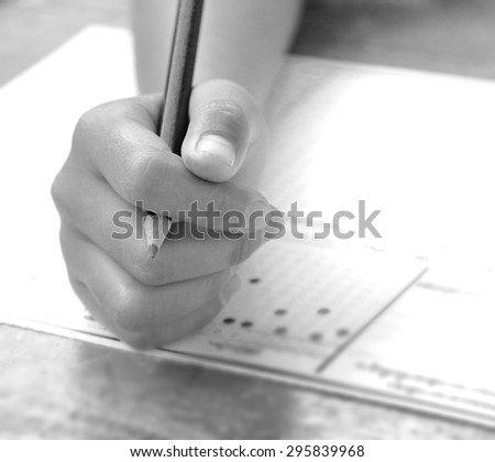 Little schoolgirl hand on examination answer sheet with black pencil in finger shot with wide aperture black and white version - stock photo