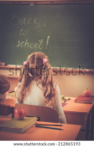 Little schoolgirl looking at blackboard in class during lesson