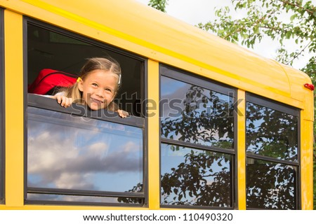 Little Schoolgirl looking through a Schoolbus Window - stock photo