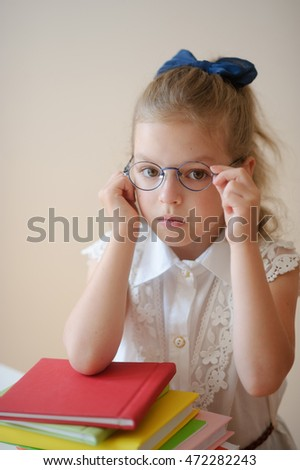 Little schoolgirl of elementary school sits lost in thought. On a school desk there is pile of textbooks. Cute schoolgirl with glasses sitting at desk resting his head on his hand.