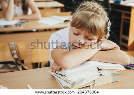 little schoolgirl sleep in classroom near blackboard - stock photo