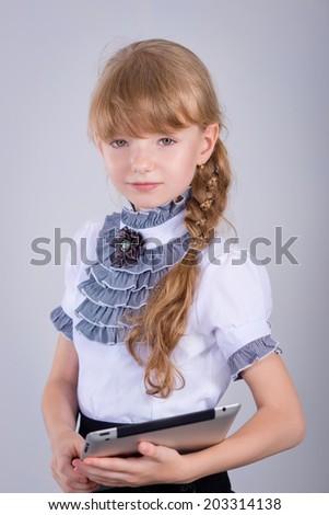 Little schoolgirl smiling while using digital tablet at desk  - stock photo