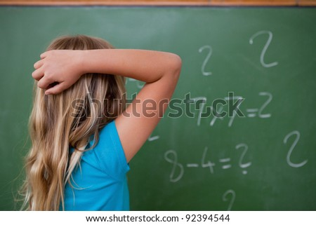 Little schoolgirl thinking while scratching the back of her head in front of a blackboard - stock photo