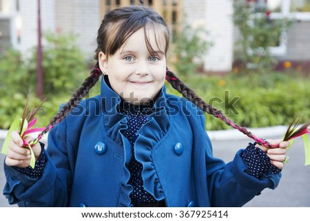 Little schoolgirl with pigtails on the street