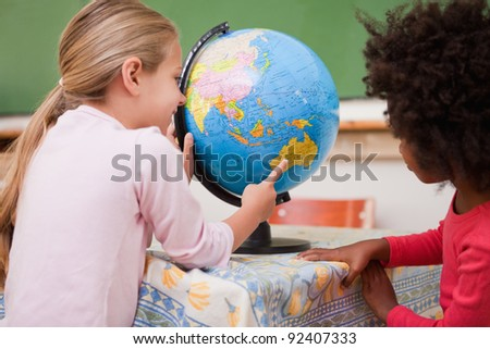 Little schoolgirls looking at a globe in a classroom - stock photo