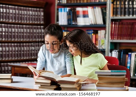Little schoolgirls reading book together while sitting at table in library