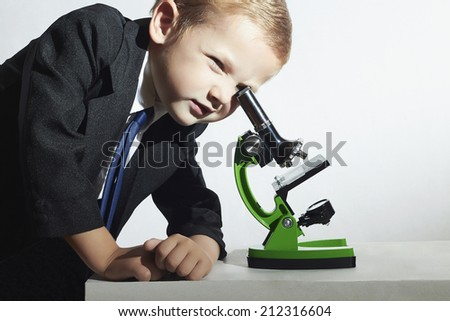 little scientist looking in microscope.fashion portrait of little boy in tie.stylish child.Schoolboy working with a microscope.Smart child.Science - stock photo