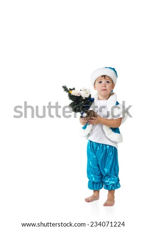 Little serious boy in a blue suit of Santa holding a Christmas tree isolated on a white background