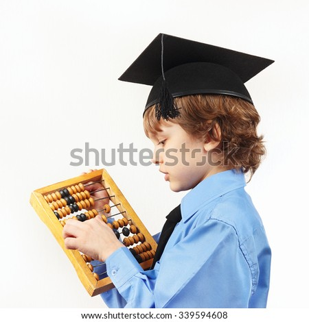 Little serious boy in academic hat with old abacus on a white background - stock photo