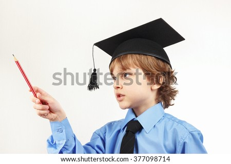 Little serious boy in academic hat with pencil on a white background - stock photo