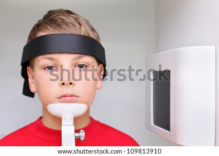 Little serious boy prepared to jaw x-ray image in dental clinic - stock photo