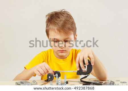 Little serious engineer plays with mechanical kit at the table
