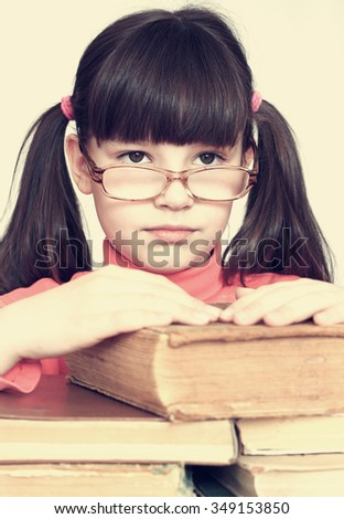 Little serious girl with glasses sitting on a pile of books. - stock photo