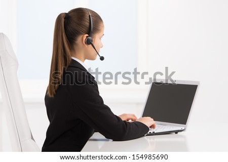 Little service representative at work. Rear view of little girl in formalwear and headset typing something on computer