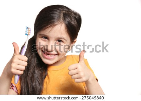Little seven year old girl shows big smile showing missing top front teeth and holding a toothbrush with thumbs up on a white background - stock photo