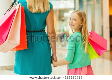 Little shopaholic. Rear view of mother and daughter holding shopping bags while little girl looking over shoulder and smiling