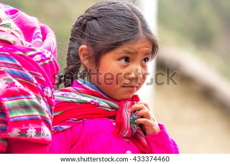Little shy Quechua tribe girl in traditional clothing in Patacancha village in Sacred Valley, Peru. 11/APR/2016 - stock photo