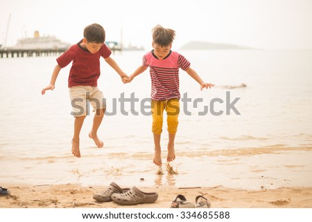 Little sibling boy jumping over the beach - stock photo