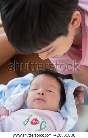 Little sibling boy kid with newborn looking each other