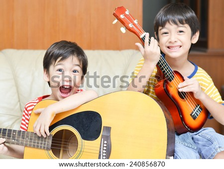 little sibling boy playing guitar and ukulele happy face - stock photo