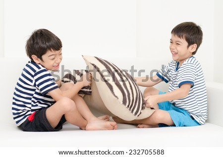 Little sibling boy playing pillow fighting on sofa - stock photo