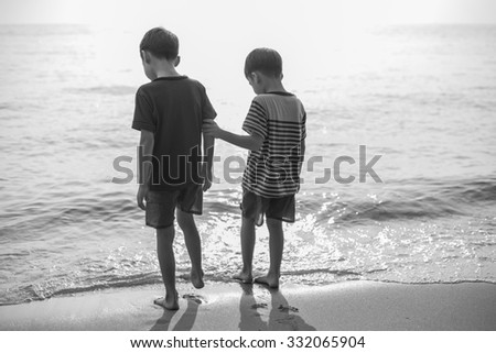 Little sibling boy standing on the beach together black and white