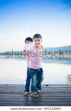 Little sibling boy standing together nearby lagoon