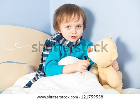 Little sick baby boy checking teddy bear's body temperature in bed