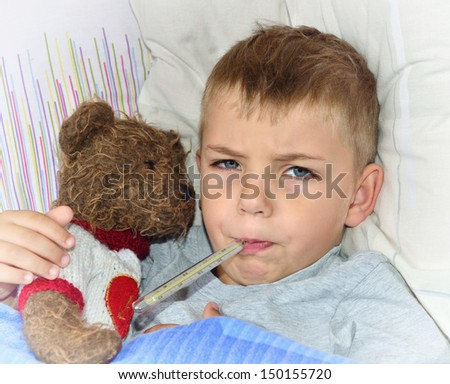Little sick boy lying in bed with fever - stock photo