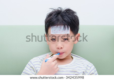 Little sick boy sitting on sofa with thermometer in mouth