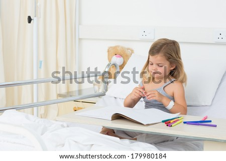 Little sick girl coloring picture book while sitting on hospital bed - stock photo