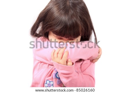 Little sick girl sneezing onto her sleeve because of sickness or allergies - stock photo