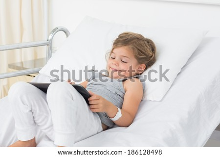 Little sick girl using digital tablet while lying in hospital bed - stock photo