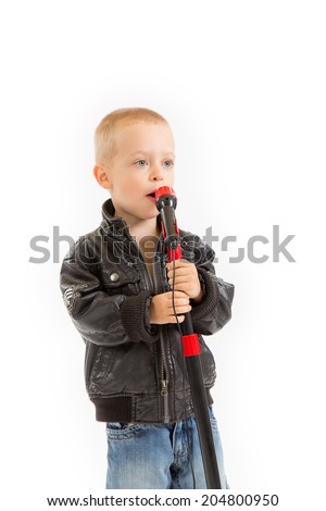 little singer boy in leather jacket singing through a microphone - stock photo