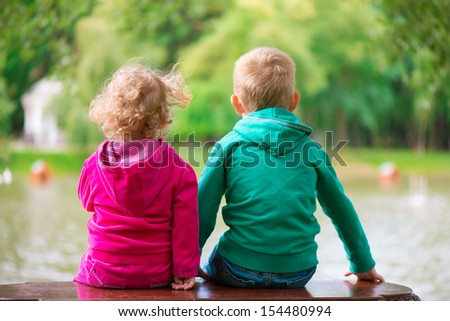 Little sister and brother sitting on bench at pond. Rear view. - stock photo