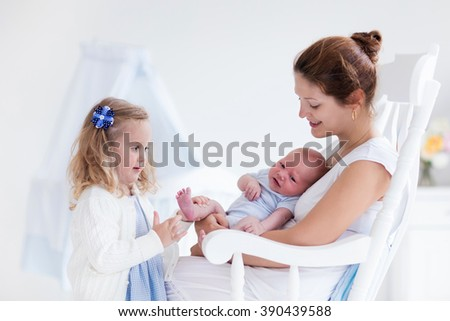 Little sister hugging her newborn brother. Toddler kid meeting new sibling. Mother and new born baby boy relax in a white bedroom. Family with children at home. Love, trust and tenderness concept.  - stock photo